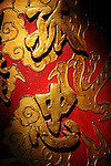 Bao-jhong Yi-min Temple, Kaohsiung -- Sunlit detail on a red temple pillar depicting a dragon's claw and the Chinese characters for 'orphan' and 'filial piety' or 'loyalty'.
