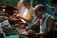 Cuba, March 1992: The Torcedores (cigar roller), rolling cigars in La Corona, The largest Cigar factory in Havana. A Torcedor in his life learns how to roll one to maximum three different size of cigars. The fastest Torcedores can roll upto 110 cigars per day.