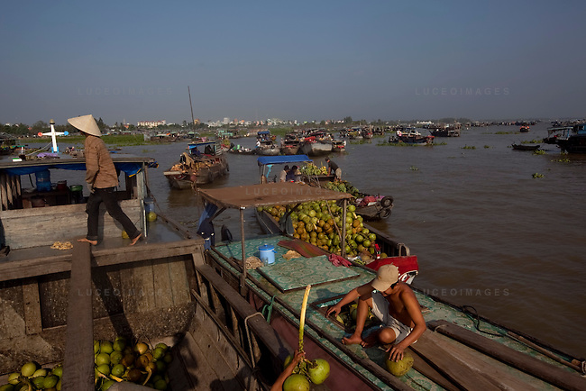 "Vietnamese traders sell coconuts at a floating market on the Hau Giang River, a tributary of the Mekong River, in Long Xuyen, the capital of An Giang Province, Vietnam. When the Mekong River reaches Vietnam it splits into two smaller riveres. The ""Tien Giang"", which means ""upper river"" and the ""Hau Giang"", which means ""lower river"". Photo taken on Monday, December 8, 2009. Kevin German / Luceo Images"