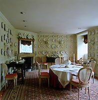 The wall panelling of the dining room has been painted to act as a background to a vast dinner service of early 18th century Ludwigsburg flower-painted porcelain