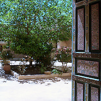 A hand-painted door leads out to one of the courtyard gardens
