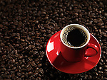 Red cup of coffee with a saucer on coffee bean background