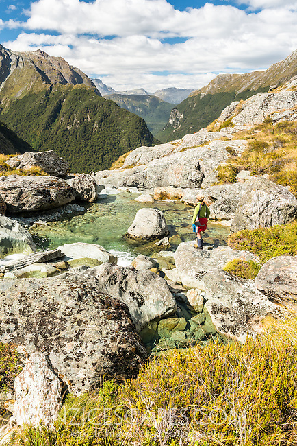 Female tramper at stream above Routeburn Falls, Mt. Aspiring National Park, UNESCO World Heritage Area, Central Otago, New Zealand, NZ