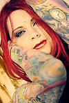 Closeup of a woman with bright red hair and green eyes with her arms covered in colorful tattoos