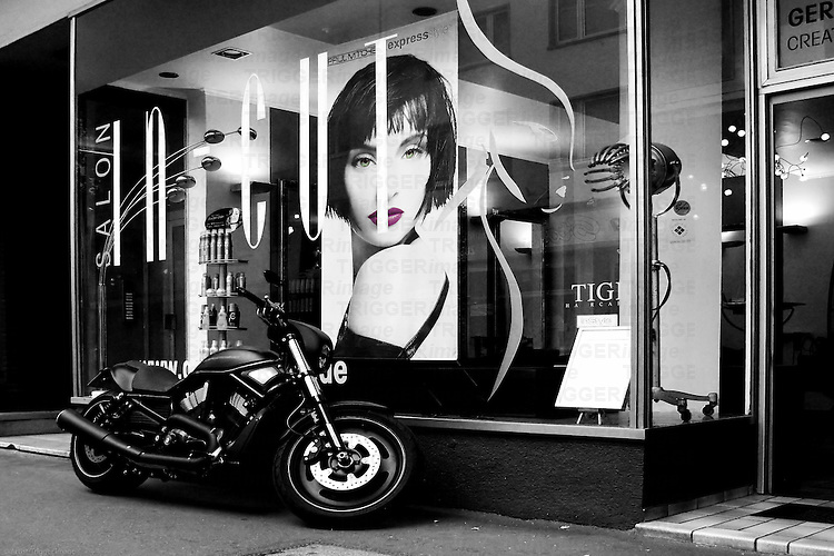 The color key of the lips of a model in a hairdresser window with a Harley Davidson in front of it.