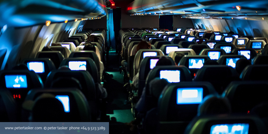 Inflight entertainment. Passenger aircraft interior photographed from behind seats, with bright video sceens being the dominant point of interest.