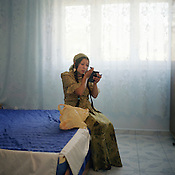Cassinca Stanescu, a Roma woman, applies mascara whilst sitting on her sons bed, in their new home. New homes such as these have been built in the last 7 years by the Roma of Sintesti, with the profits from their scrap metal dealing..