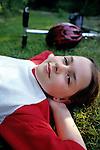 Young girl, (10-12 yrs old)  with hands behind head daydreaming, looking at camera, Lake Pleasant, Bothell, Washington USA  MR