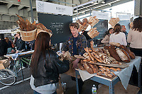 """Customers shop at Bien Cuit bakery at the New Amsterdam Market on South Street in New York during the market's opening day for the season, Sunday, April 29, 2012. The market, located in the former Fulton Fish Market, features vendors who source their artisanal food directly from local farmers and stands of the farmers'  themselves . For opening day they promoted their """"Bread Pavilion"""" which had booths from 16 local artisanal bakeries. (© Richard B. Levine)"""
