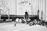 A homeless man sits on sidewalk by a railway station in central Tokyo, Japan.