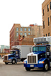 Two refrigerated trucks are loaded with meat in the packing district of Chicago.