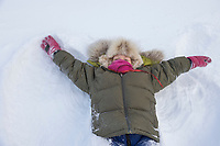 Leo Hicker dressed in a winter parka with a wolf ruff enjoys makes a snow angel in Wiseman, Alaska, Arctic