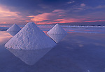Pyramids of salt reflect the pink hues of predawn light rising above Bolivia's Salar de Uyuni. The salar, fifteen thousand square kilometers in size, is but a remnant of an ancient lake that filled the vast depression nestled between two branches of the Andean Range.  The man-made pyramids are formed when local Bolivians rake the salt on the salar's surface into piles.