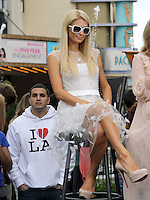 "Paris Hilton .Gabriel Mann And Kathy And Paris Hilton Fashion Show On ""Extra"" Held at The Grove, West Hollywood, California, USA..May 2nd, 2012.full length white sheer dress tulle sitting sunglasses shades.CAP/ADM/KB.©Kevan Brooks/AdMedia/Capital Pictures."
