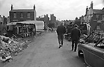 Gypsy inner city camp site Balsall Heath Birmingham UK 1967. Men walking towards houses on Emily Street and what might be the junction with Upper Highgate Street. <br />