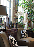 Next to an interesting collection of obelisks a scaled-down copy of the VIctory of Samothrace creates a dramatic note in this elegant corner of the living room