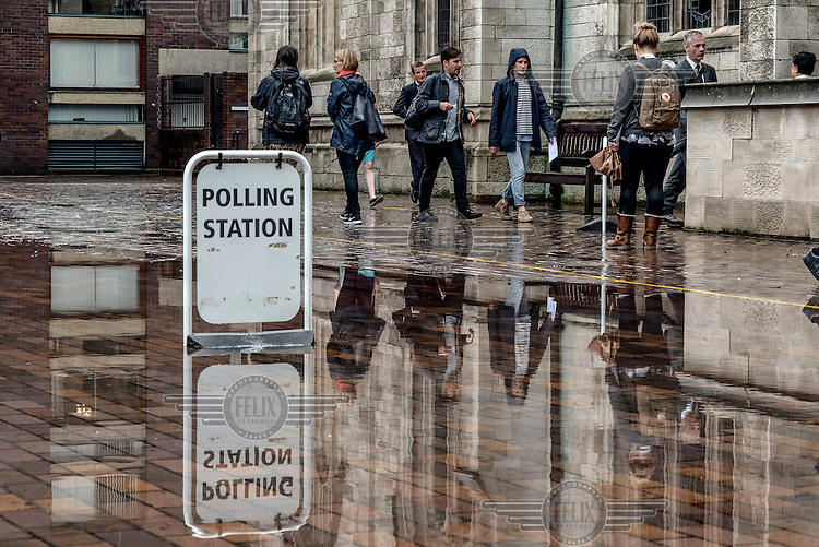 People walk past a polling station sign on a flooded pavement beside St Giles Cripplegate church near the Barbican Centre in the City of London.