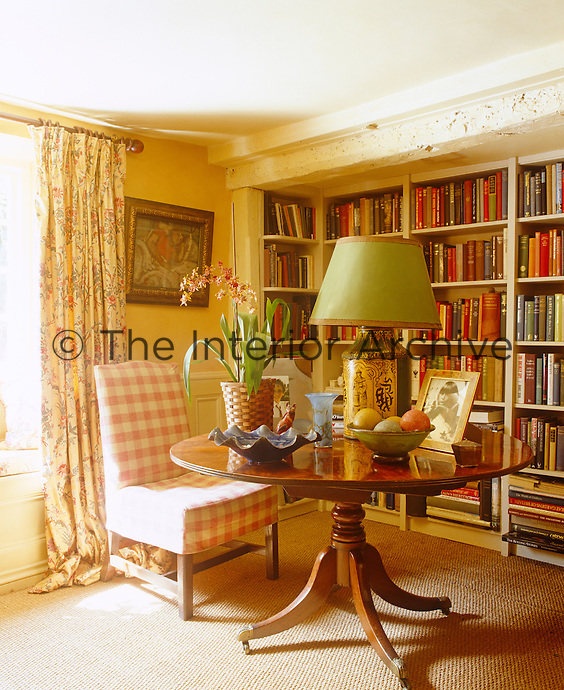 One wall of the country living room is lined with bookshelves and is furnished with a round mahogany table