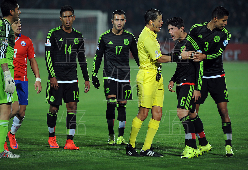 SANTIAGO- CHILE - 15-06-2015: Victor Carrillo, árbitro peruano, detiene a Javier Guemez (Der.) jugador de Mexico durante partido Chile y México, por la fase de grupos, Grupo A, de la Copa America Chile 2015, jugado en el estadio Nacional Julio Martinez la Ciudad de Santiago. / Victor Carillo, peruvian referee, stop to Javier Guemez (R.) Mexico player during the match between Chile and Mexico, for the group stage Group A of the Copa America 2015 Chile, played at the National Stadium Julio Martinez in Santiago City. Photos: VizzorImage / Alfredo Gutierrez / Cont.
