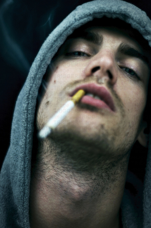 A young man with head leaning back smoking a cigarette