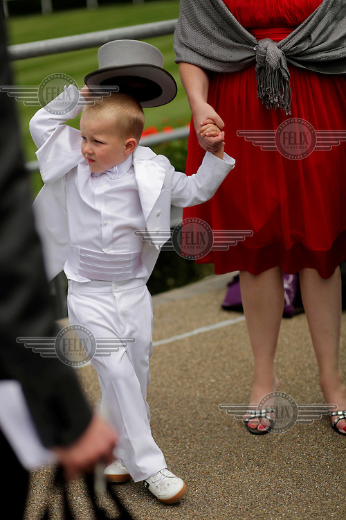 A young racegoer, dressed in a white suit and miniture top hat, at the Royal Ascot race meeting. The annual event, during which each day begins with the Queen's arrival in a horse drawn carriage, dates back to 1711 when Queen Anne organised the first races on what was then a heath near Windsor Castle.