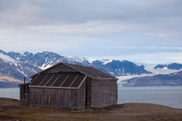 Wooden shack on the edge of Kongsfjord, with glacier in the background at the international scientific research base of Ny Alesund, Svalbard.
