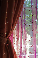 A pink embroidered sheer complements the curtain tied back against a bedroom window