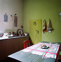 The kitchen is simple with its plain units and painted wooden breakfast table