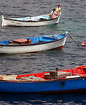 Two boys sit in a fishing boat in the shadows of Monte Brasil onTerceira, Azores. Fishing is one of the main industries for residents on these islands.Far out in the Atlantic Ocean, some 850 miles off the western coast of Lisbon, Portugal lies the 425-mile long archipelago of the Azores. (Jim Bryant Photo)....