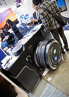 A very large model camera being used as a desk at an exhibition to gain interest.