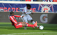 New York forward Peguy Luyindula (88) shoots the ball before sliding Chicago defender Jalil Anibaba (6) can make the block.  The Chicago Fire defeated the New York Red Bulls 3-1 at Toyota Park in Bridgeview, IL on April 7, 2013.