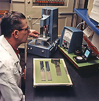 Instrumentation engineer examines the properties of metals used in Ford cars. Ford Motor Company, Dearborn, Michigan, 1966. Photo by John G. Zimmerman.