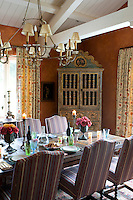 Pattern and colour feature highly in the dining room with sponged russet walls, floral curtains and dining chairs upholstered in striped cotton