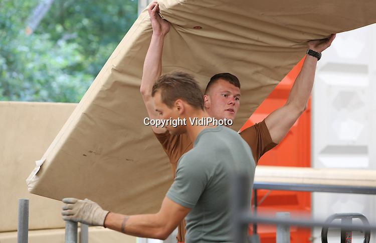 Foto: VidiPhoto<br /> <br /> NIJMEGEN - Op militair kamp Heumensoord bij Nijmegen wordt maandag flink aangepakt voor de opbouw en inrichting van de tenten voor de Vierdaagse. Er komen zo'n 45 enorme manschappenverblijven voor 6000 militairen -van wie er 5000 mee lopen- uit 32 landen. Evenals vorig jaar wordt het meeste werk verzet door personeel van Defensie, waardoor het inhuren van uitzendkrachten niet meer nodig is en er flink op de kosten kan worden bespaard. De inrichting van Heumensoord komt ten laste van het Defensiebudget. Zelfs met de individuele (dieet)wensen van de militairen wordt rekening gehouden. Zo zijn er halalmaaltijden en is er zelfs een gebedshoekje voor moslims. Aan de internationale wandelvierdaagse van Nijmegen, die op 15 juli van start gaat, doen 42.000 wandelaars uit in totaal 72 nationaliteiten mee. De Vierdaagse is het grootste wandelevenement ter wereld.