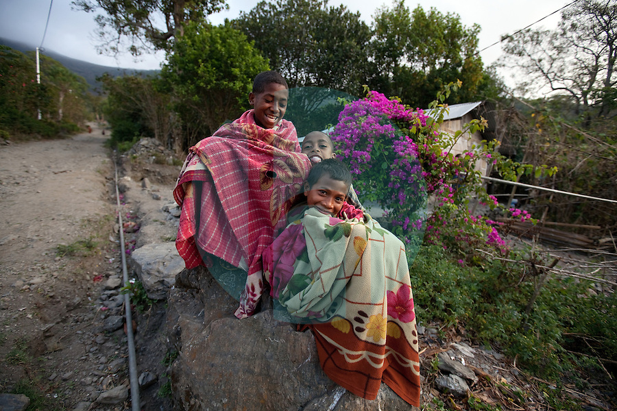 To protect themselves from the cool morning air, children wrap themselves in blankets in the mountain town of Laclubar, Timor-Leste on Wednesday, Oct. 19th, 2011.  Photographer: Daniel J. Groshong/The Hummingfish Foundation