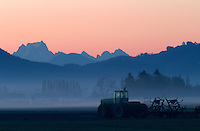 Tractor in field at sunrise with Cascade Mountains in background, Mount Vernon, Skagit Valley, Skagit County, Washington, USA