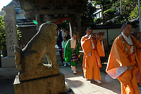 Shingon Buddhist priests at Yakuouin temple, Mount Takao. They are blowing conch horns.