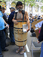 USA. New York City. Occupy Wall Street (OWS) is a people-powered movement that began on September 17, 2011 in Liberty Square in the Wall Street financial district of Manhattan. The protesters have created a small campsite at the Zuccotti Park site. OWS and has spread to over 100 cities in the United States and actions in over 1,500 cities globally. OWS is mainly protesting social and economic inequality, corporate greed, corruption and influence over government&mdash;particularly from the financial services sector&mdash;and lobbyists.  It is fighting back against the corrosive power of major banks and multinational corporations over the democratic process, and the role of Wall Street in creating an economic collapse that has caused the greatest recession in generations. The protesters' slogan, &quot;We are the 99%&quot;, refers to the difference in wealth and income growth in the U.S. between the wealthiest 1% and the rest of the population. OWS aims to expose how the richest 1% of people are writing the rules of an unfair global economy that is foreclosing on our future. OWS has being organized using a non-binding consensus based collective decision making tool known as a &quot;people's assembly&quot;. Naked man in wood barrel. Bare feet. Poor man nation. Laptop computer Mac Book Pro.20.10.2011 &copy; 2011 Didier Ruef