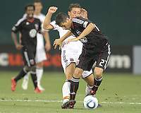 Branko Boskovic #27 of D.C. United gets away from Marc Wilson #8 of Portsmouth FC during an international friendly match at RFK Stadium on July 24 2010, in Washington D.C. United won 4-0.