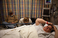 Shelia Burnett, lays in a hospital bed with her daughter Lauren and husband Nelson at her side as they wait for her to go into surgery.
