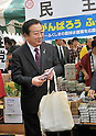 April 28, 2012, Tokyo, Japan - Japan's Prime Minister Yoshihiko Noda buys souvenir of some souvenir of agricultural products grown in the nation's northeastern region stricken by the March 11 earthquake and tsunami during a May Day rally in Tokyo on Saturday, April 28, 2012. As a guest speaker, Noda addressed some 35,000 people attending the rally sponsored by the Japanese Trade Union Confederation. (Photo by Natsuki Sakai/AFLO) AYF -mis-