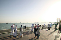 Qatar. Doha. Locals walking on the corniche  along the seaside.