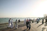 Qatar. Doha. Locals walking on the corniche  along the seaside.