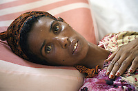 Somaliland. Sahil province. Berbera. Tubeculosis (TB) hospital. Female ward. Portrait of a young black muslim woman, a TB patient, lying in her bed while she is taking the two months drugs as a TB treatment. The Global Fund through the ngo ( Non-governmental organization ) World Vision supports the programm with a Tuberculosis grant (financial aid). Somaliland is an unrecognized de facto sovereign state located in the Horn of Africa.  © 2006 Didier Ruef