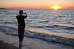 Teenager Boy Taking a Photo with Cell Phone, Silhouette at Sunset on Beach