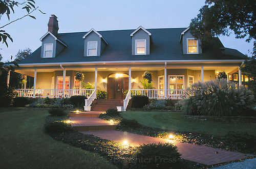 Lovely cape cod style home at dusk lit for an evening party, Midwest USA