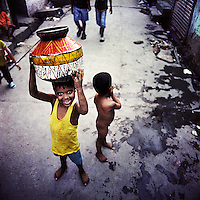 A child on his way to collect water in the Kathputli Colony.  Located in northwest Delhi, Kathputli is inhabited by approximately 2,000 performing artists, practicing traditional art forms such as marionette puppetry, juggling, magic, acrobatics, dance and music. Many have travelled all over the world showcasing their abilities, but they still choose to remain living in this slum, which is one of the most impoverished in the city.