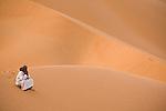 A man sits alone on the sand dunes of the Empty Quarter, Ar Rub Al Khali, Oman.