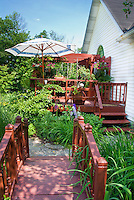 Darling garden bridge walkway path in small backyard garden with deck, house, umbrella, on sunny summer day