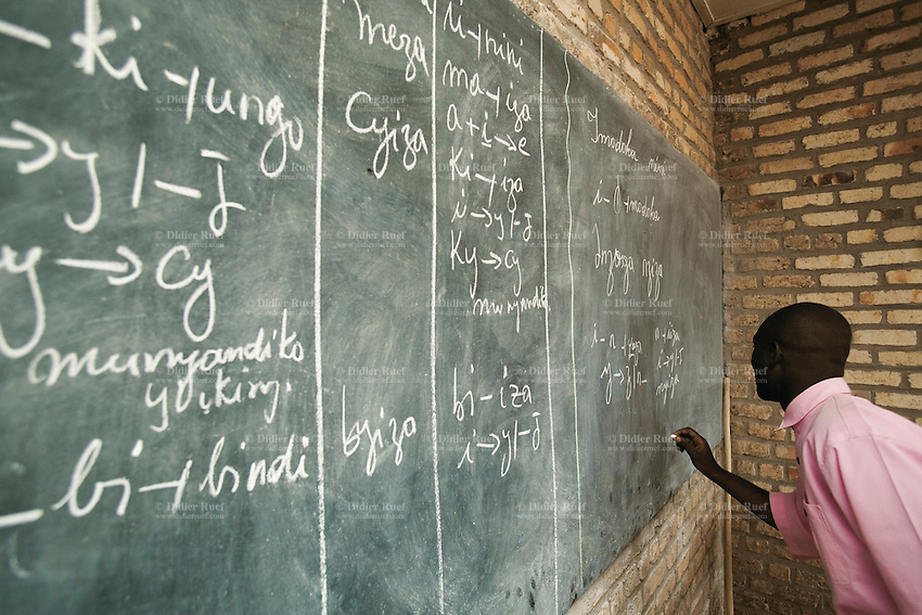 Rwanda. Southern province. District of Muhanga. Central jail of Gitarama. A group of black teenagers boys, wearing the pink prisoner's clothes during the Kinyarwanda language class. An adolescents writes words with a chalk on a blackboard. Bricks wall. Minors block. Minors in detention. Detention pending trial and after trial, sentenced to prison. The non-governmental organization (NGO) Fondation DiDé - Dignité en détention runs the Encademi (Encadrement des mineurs) program. Prison centrale de Gitarama. Quartier des mineurs.  © 2007 Didier Ruef